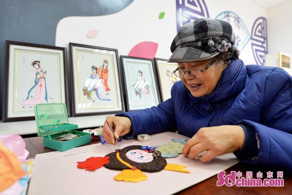 <br/>  2月8日,临近春节,青岛辽源路街道的唐秀娟老人通过剪刀、布头、棉线这些普通的物件,创作了一组精美的《金陵十二钗》人物像。图为唐秀娟老人在制作人物贴画。<br/>