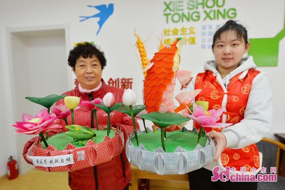 <br/>  2月8日,青岛辽源路街道,毛新美老人(左)展示丝网花作品。<br/>