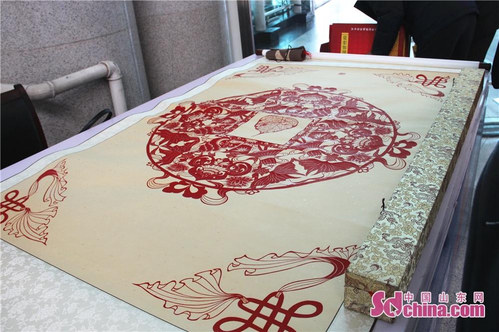 <br/>  一幅剪纸引得许多旅客围观,记者了解到,这幅作品名为般若智,内容为佛教的八吉祥,从构思到制作完成用时半年之久。<br/>