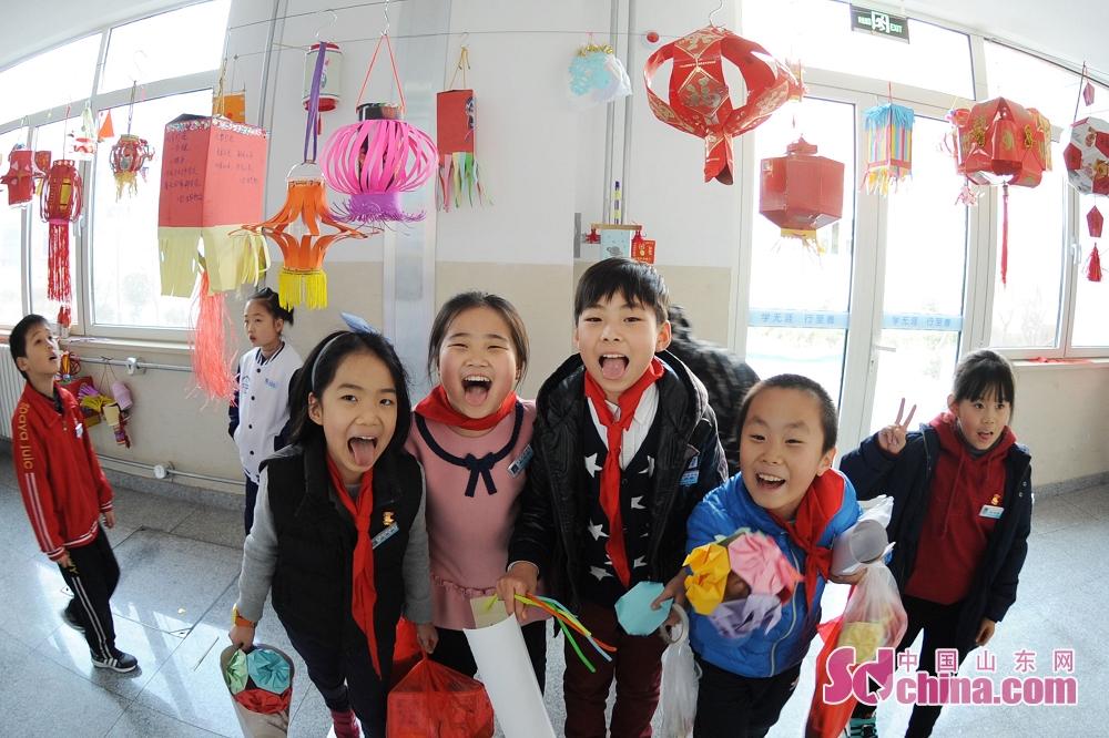 <br/>  小学生在自己制作的&amp;ldquo;低碳环保花灯&amp;rdquo;下扮笑脸、过元宵。<br/>