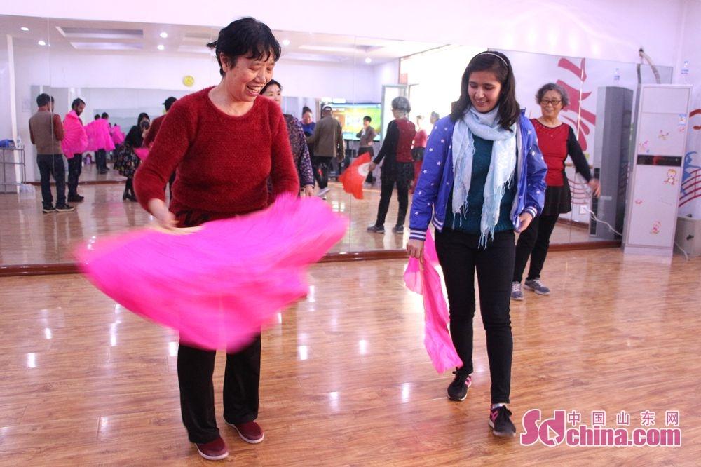 <br/>  外国友人跟老人学习扇子舞。