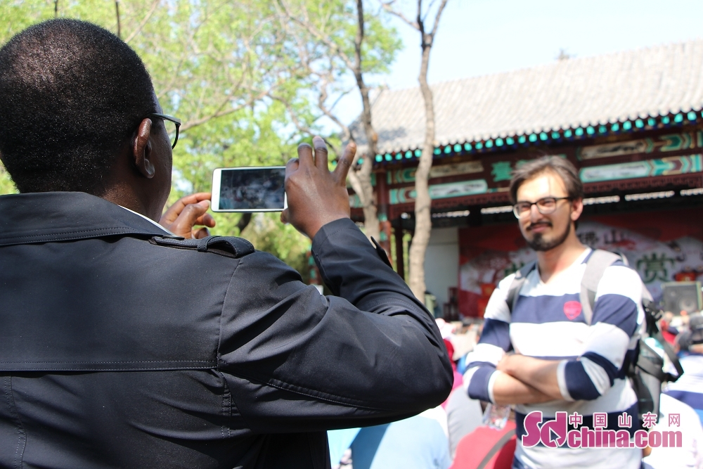 Two foreigners take photos in the temple fair. Recently, seven foreigners paid a visit to Qianfoshan temple fair to get a close look at Chinese temple-fair culture in Jinan, east China&amp;rsquo;s Shandong Province.<br/>