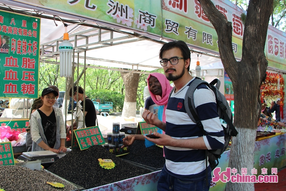 Two foreigners stop at a stall of Chinese herb medicine. Recently, seven foreigners paid a visit to Qianfoshan temple fair to get a close look at Chinese temple-fair culture in Jinan, east China&amp;rsquo;s Shandong Province.<br/>