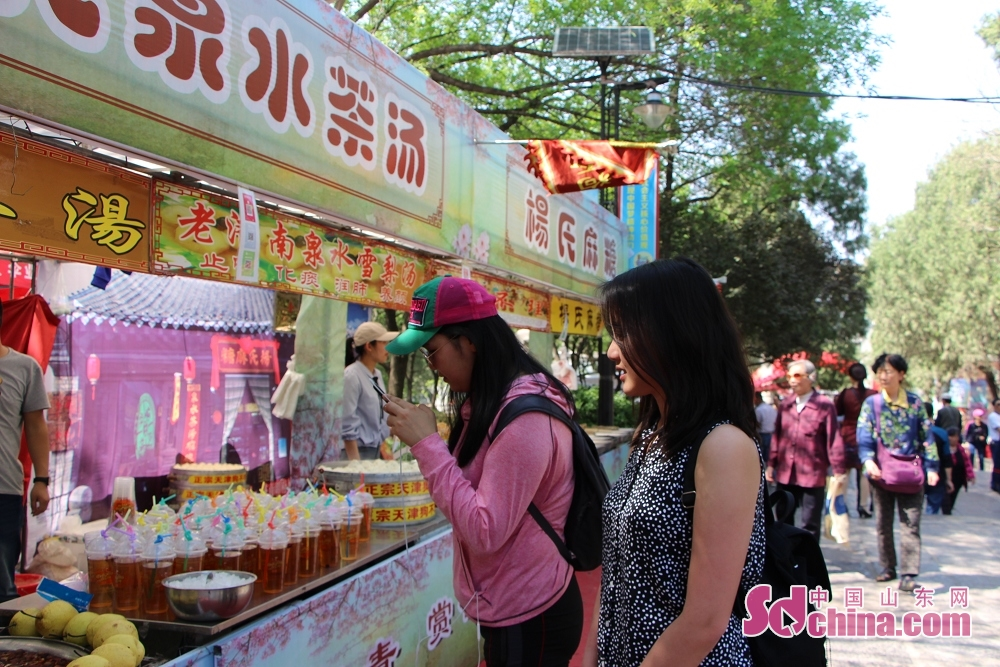 Two foreigners select goods in the front of a stall. Recently, seven foreigners paid a visit to Qianfoshan temple fair to get a close look at Chinese temple-fair culture in Jinan, east China&amp;rsquo;s Shandong Province.<br/>