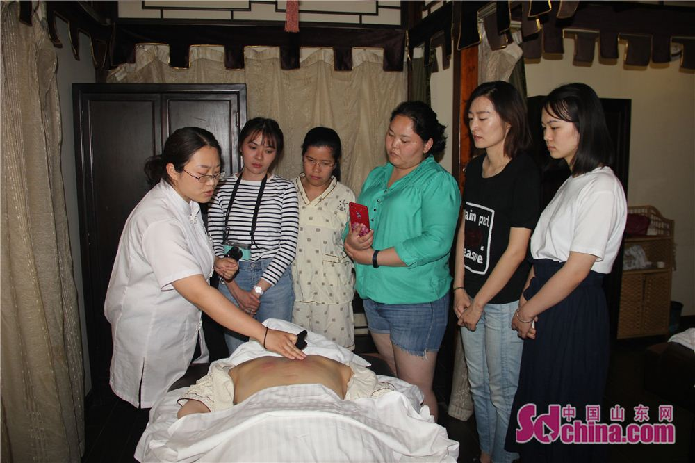 A therapist explains the techniques of scrapping therapy in Taijingtang in Jinan, east China&amp;rsquo;s Shandong Province. Four foreign students, studying in Shandong Normal University, went to Taijingtang in Kuanhouli in Jinan to learn TCM therapies recently.<br/>