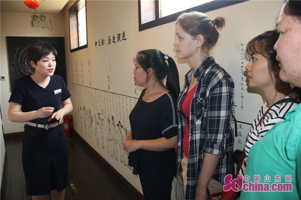 A staff member of Tiajingtang introduces history and development of TCM to foreigners in Jinan, east China&amp;rsquo;s Shandong province. Four foreign students, studying in Shandong Normal University, went to Taijingtang in Kuanhouli in Jinan to learn TCM therapies recently.<br/>