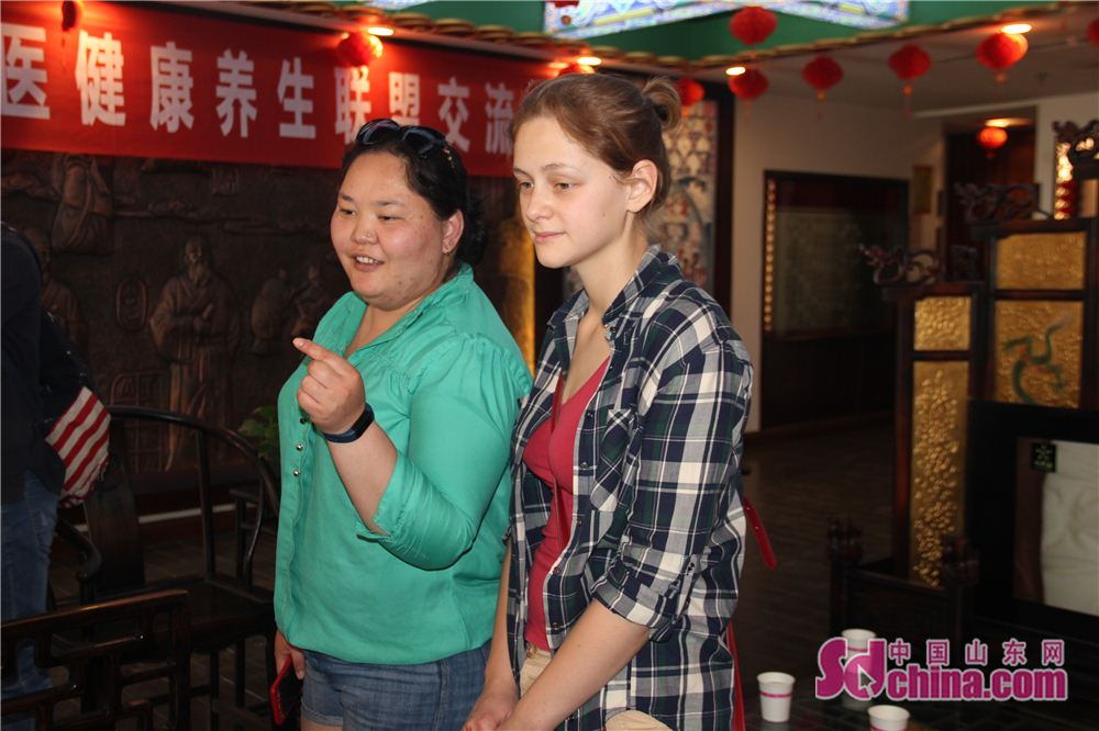 Two foreigners discuss the acupuncture needle in Taijingtang in Jinan, east China&amp;rsquo;s Shandong Province. Four foreign students, studying in Shandong Normal University, went to Taijingtang in Kuanhouli in Jinan to learn TCM therapies recently.<br/>