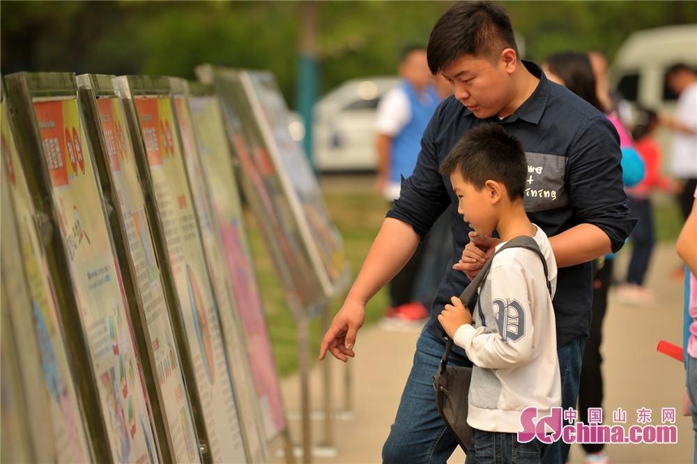 <br/>        一名小学生在家长带领下学习防震减灾知识。