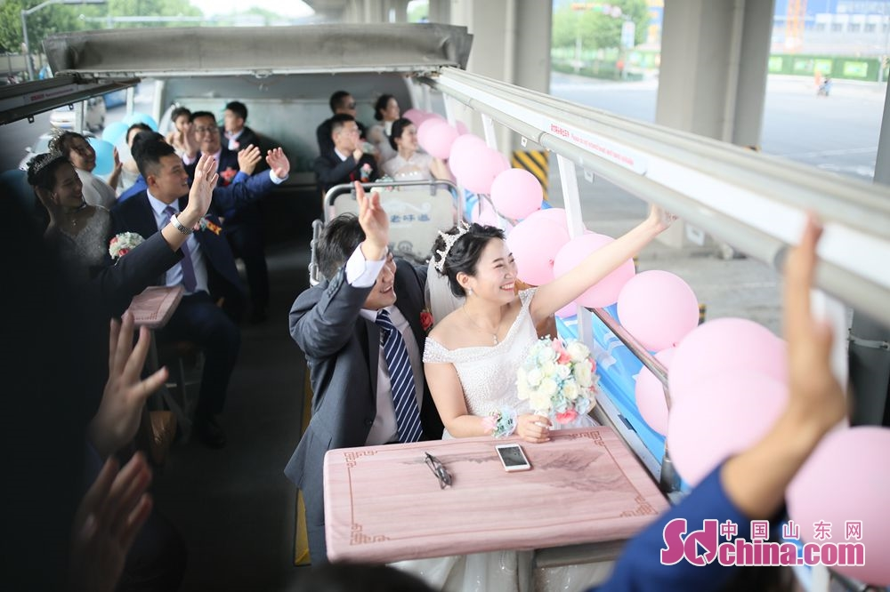 New couples wave to the passerby in Jinan, capital of east China&amp;rsquo;s Shandong Province. Recently, six couples of the Second Construction Limited Company of CCEED, taking bus as wedding cars, joined a group wedding ceremony here.<br/>