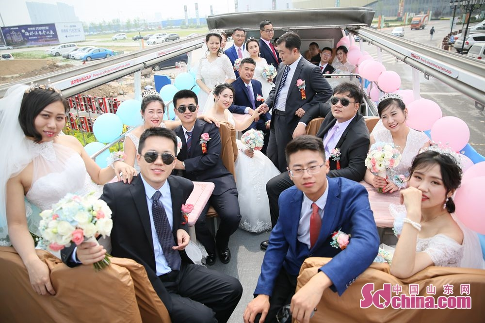 New couples pose for a group photo in Jinan, capital of east China's Shandong Province. Recently, six couples of the Second Construction Limited Company of CCEED, taking bus as wedding cars, joined a group wedding ceremony here.