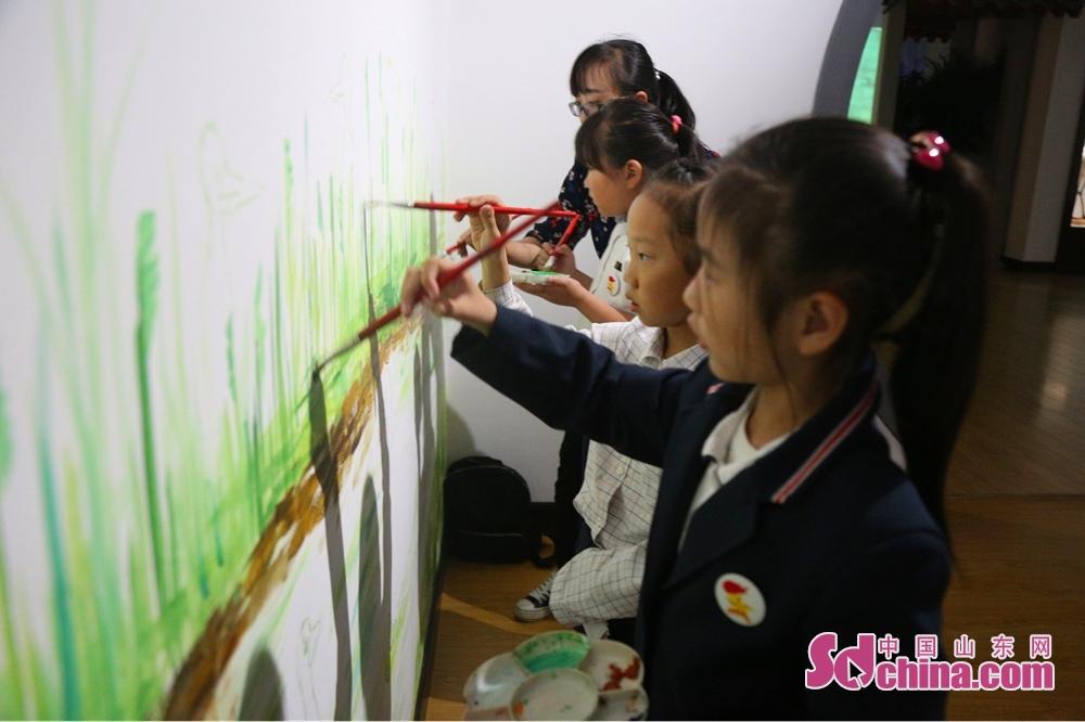 <br/>             学生正在墙上绘画。