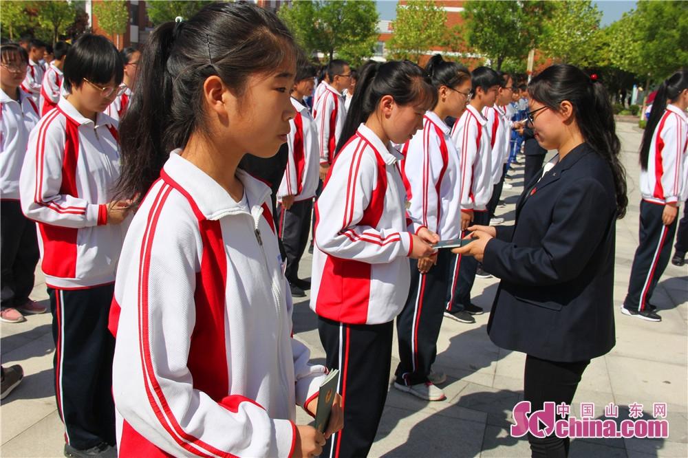 <br/>  仪式中,青年团员教师代表为65名新团员佩戴团徽、颁发团员证书。(摄影 隋涛)<br/>