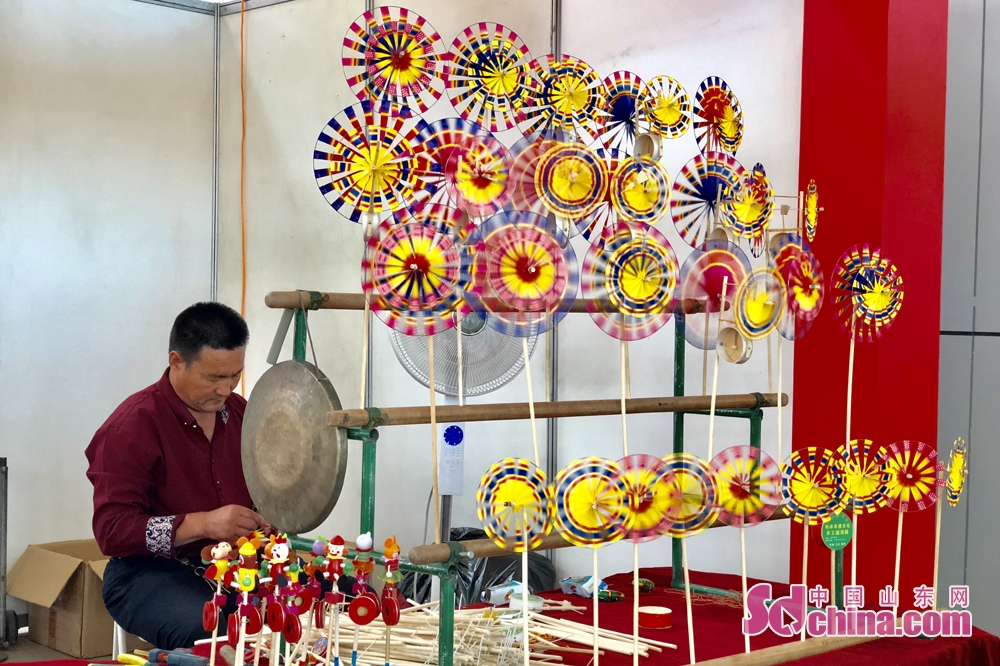 "An artisan makes pinwheel at the Sixth Shouguang Cultural Industries Fair on May 8 in Shouguang City, Shandong Province. Shouguang Cultural Industries Fair, with the theme of ""be confident in our culture and construct noted cultural city"", covers a total area of 1,100 meters and sets up 80 exhibition booths. (sdchina.com/Han Beibei)"