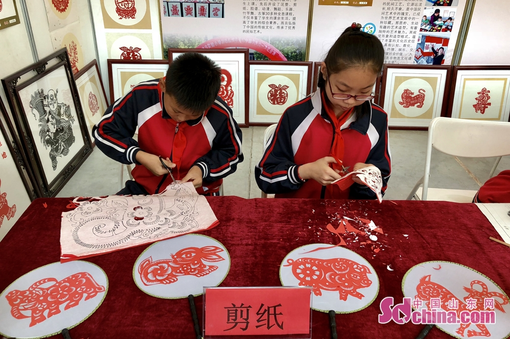 Two students make paper-cutting at the Sixth Shouguang Cultural Industries Fair on May 8 in Shouguang City, Shandong Province. Shouguang Cultural Industries Fair, with the theme of &amp;ldquo;be confident in our culture and construct noted cultural city&amp;rdquo;, covers a total area of 1,100 meters and sets up 80 exhibition booths. (sdchina.com/Han Beibei)<br/>