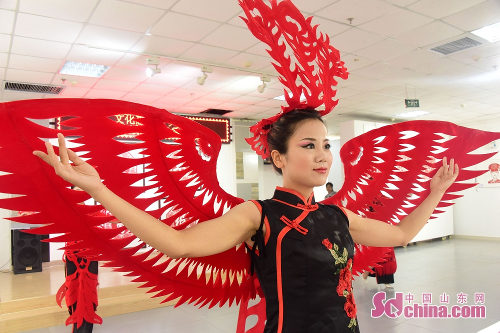 A model presents paper cutting creation of Huang Yuhua, Dong Yueqin and Tiantian during the second excellent paper cutting work exhibition in Chiping of Liaocheng, Shandong Province, on June 25, 2018.<br/>