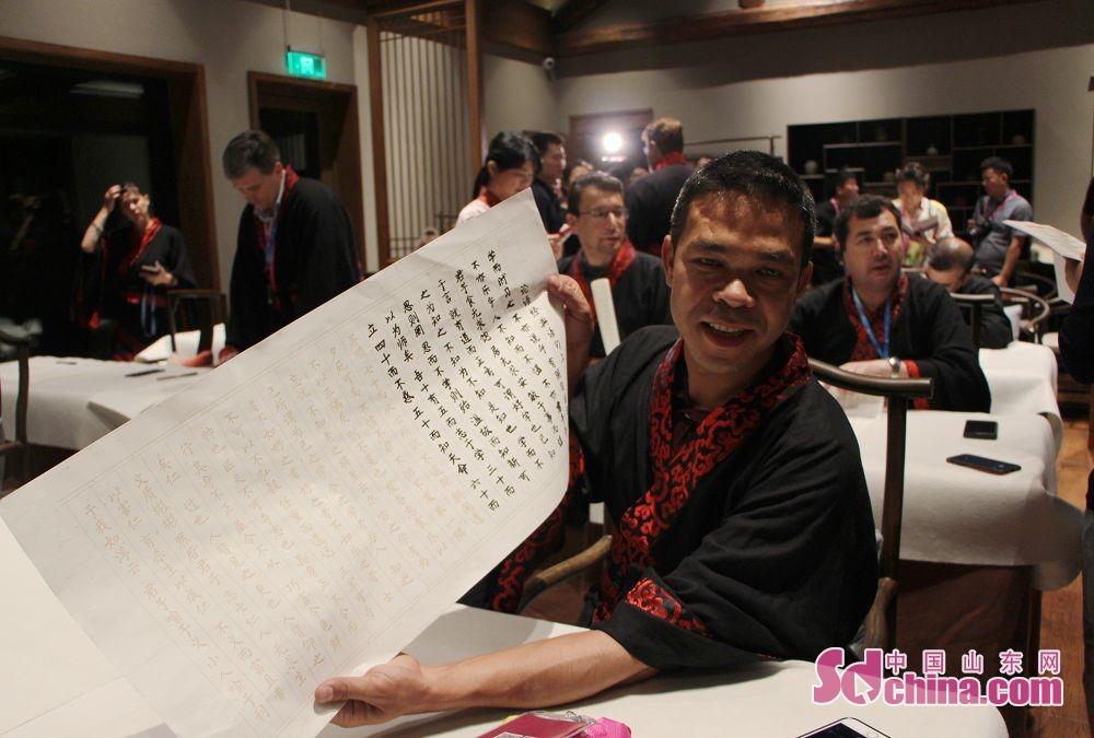 外国友人展示自己抄写的《论语》作品。(摄影 胡立荣)<br/>