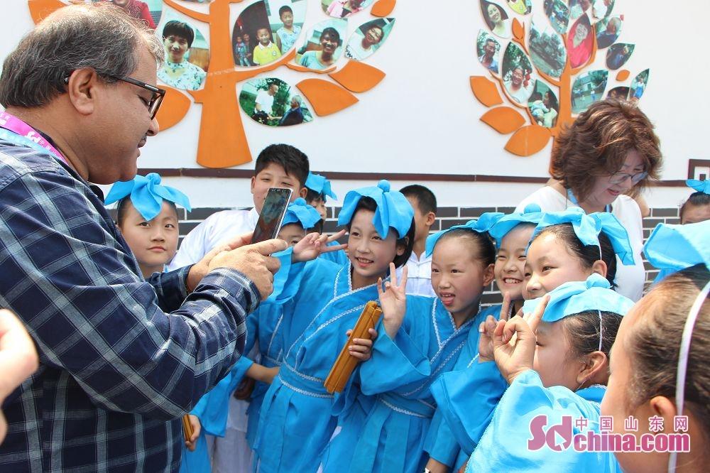 图为活动结束后,外国友人与孩子们亲密互动。(摄影 胡立荣)<br/>