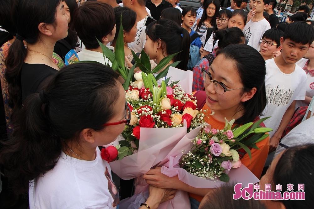 <br/>  6月8日下午5点,2018年高考结束,济宁市育才中学考点门口,家长们抱着鲜花为考生献上祝福。