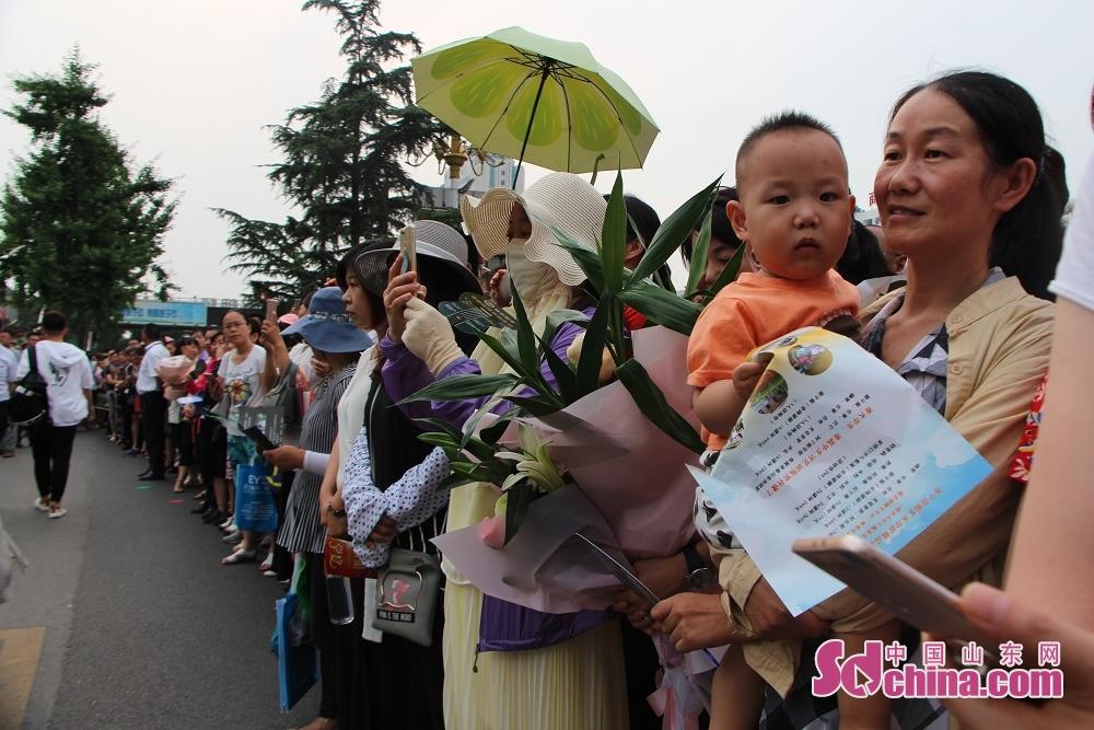 <br/>  家长们拿着鲜花在考点门口等待考生走出考场。