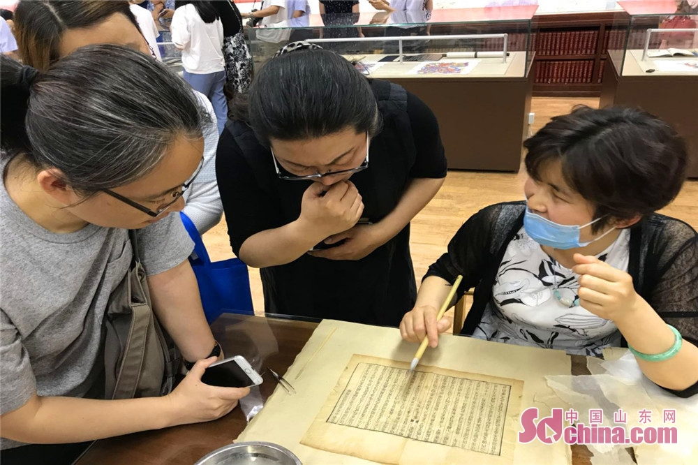 A restorer of ancient books explains the reparation process of the Genealogy of Fan&amp;rsquo;s Family to visitors in Jinan, east China&amp;rsquo;s Shandong Province. Shandong Precious Ancient Books Exhibition kicked off in Shandong Library on June 9 and will last to June 29, 2018.<br/>