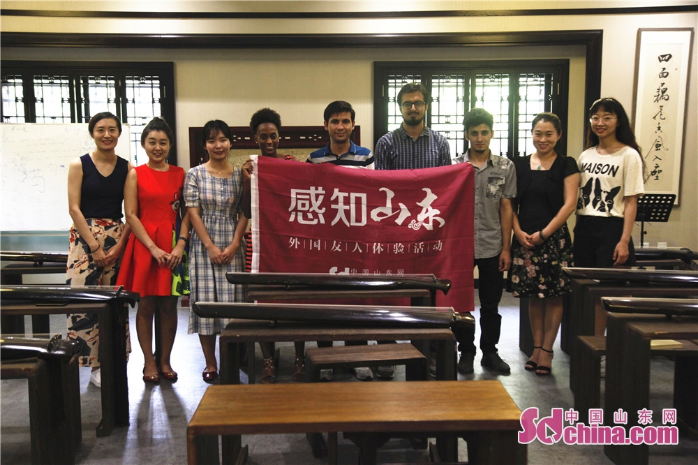 Foreigners and teachers pose for a group photo after the activity. Five foreigners from different countries went to Ni Shan Academy to learn Guqin, a string instruments of Chinese zither family, in Daming Lake of Jinan, east China's Shandong province.