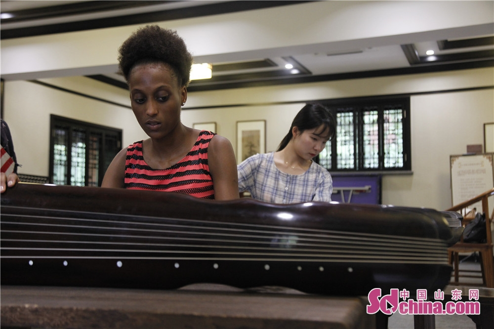 A foreigner observes the structure of Guqin. Five foreigners from different countries went to Ni Shan Academy to learn Guqin, a string instruments of Chinese zither family, in Daming Lake of Jinan, east China&amp;rsquo;s Shandong province.<br/>