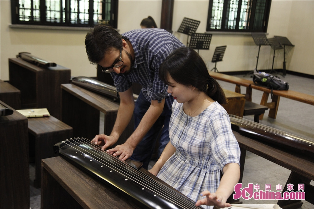 Two foreigners discuss the methods to play Guqin. Five foreigners from different countries went to Ni Shan Academy to learn Guqin, a string instruments of Chinese zither family, in Daming Lake of Jinan, east China&amp;rsquo;s Shandong province.<br/>