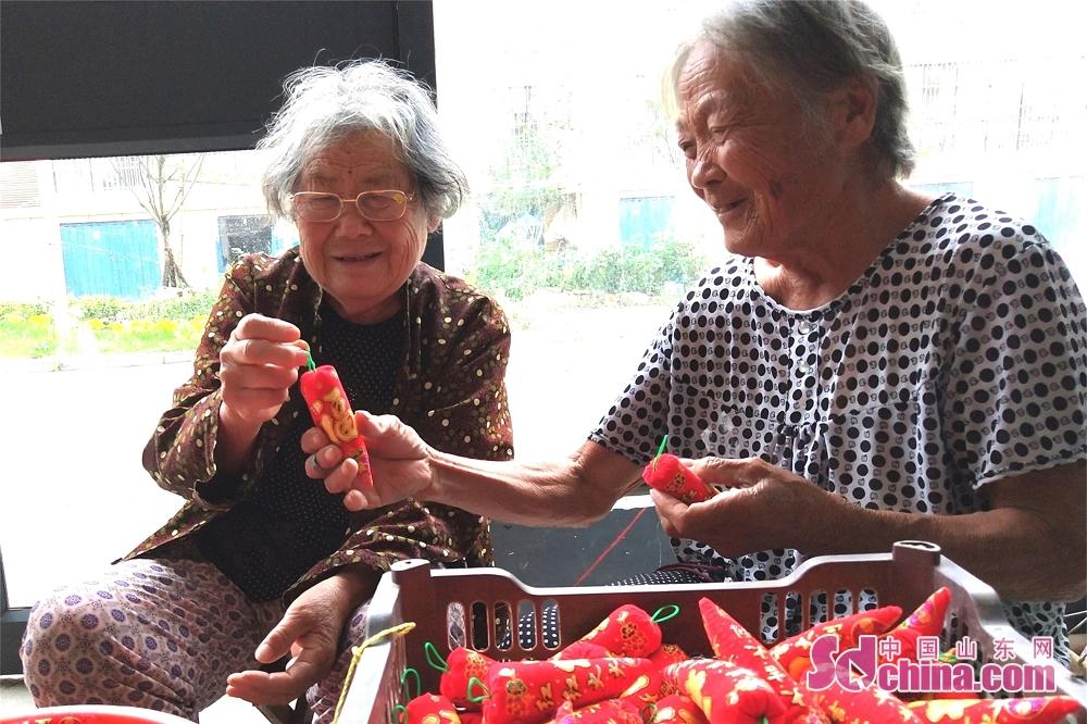 <br/>  在山东省郯城县马头镇有老姊妹俩,姐姐刘玉英今年82岁,妹妹刘玉兰77岁,她们都有着干手工活的&amp;ldquo;好手艺&amp;rdquo;。如今,虽然年龄大了,但还是闲不惯,坚持自食其力。她们从工艺品厂领来了&amp;ldquo;红辣椒&amp;rdquo;,进行填充缝制赚取零花钱,一周能缝制好1000个&amp;ldquo;红辣椒&amp;rdquo;。近日,在郯城县马头镇玉带社区老年公寓的楼道里,姐姐刘玉英(右)在指导妹妹刘玉兰(左)缝制&amp;ldquo;红辣椒&amp;rdquo;的技巧。<br/>