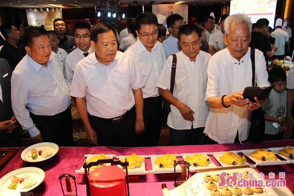 <br/>  孔府菜专家、学者在东方儒家酒店集团展位前驻足拍摄。<br/>