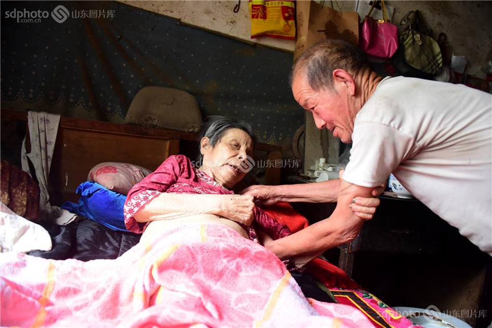 <br/>  山东省茌平县温陈街道温庄村今年82岁的张之祥老人,照顾因偏瘫卧床的妻子张兰英已有18个年头。18年前时年62岁的妻子,因脑梗落下偏瘫的后遗症,起居、饮食、穿衣、大小便全靠人伺候,在张之祥的精心照顾下妻子硬是挺过了危险期。史奎华摄(图片版权归山东图片库所有,未经授权严禁转载)<br/>
