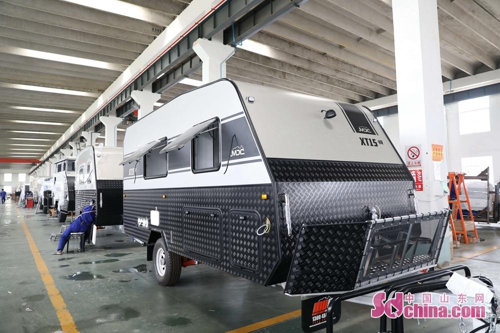 <br/>  7月27日,在山东省荣成市名骏户外休闲用品有限公司,工人们正在检查成品房车。