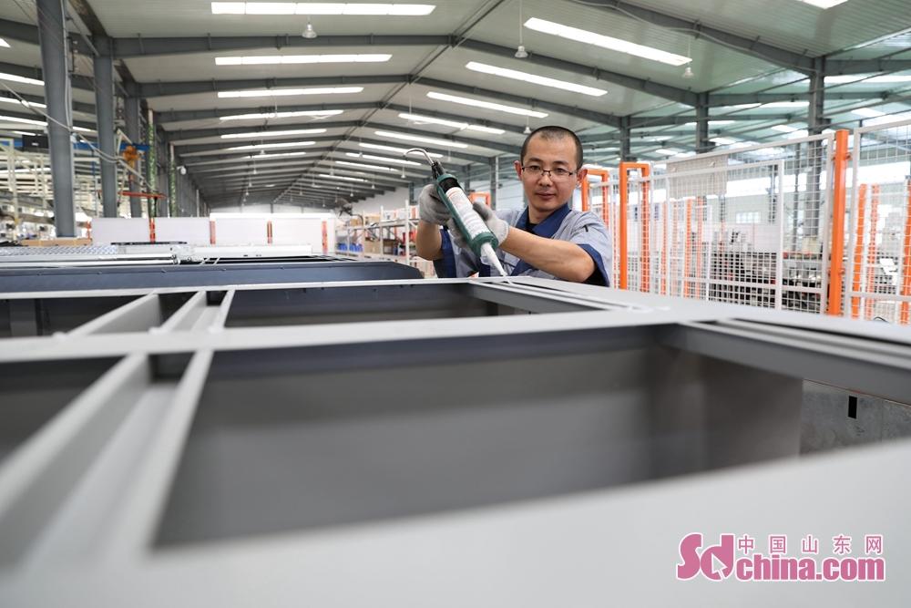 <br/>  7月27日,在山东省荣成市名骏户外休闲用品有限公司一生产车间,工人们正在赶制房车。<br/>