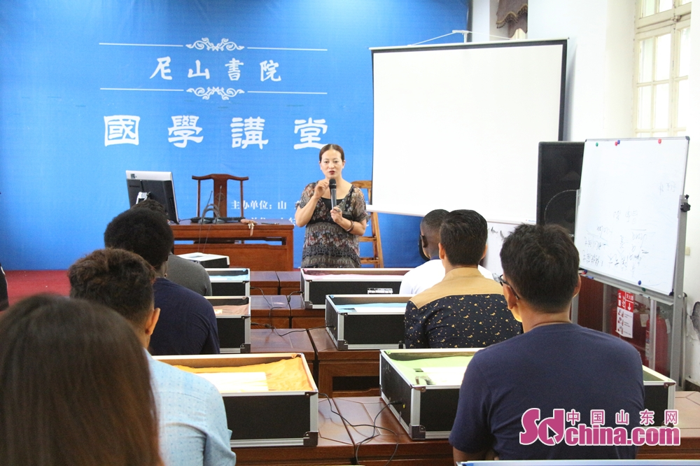 A teacher teaches foreigners how to draw sand painting in Ni Shan Academy in Daming Lake of Lixia District, Eastern China's Shandong Province. 8 foreigners from different went to Ni Shan Academy to learn sand painting. (Sschina.com/Li Zhen)<br/>