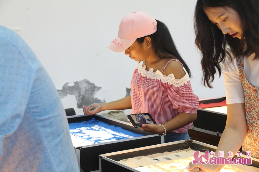 Two foreigners draw sand painting in Ni Shan Academy in Daming Lake of Lixia District, Eastern China's Shandong Province. 8 foreigners from different went to Ni Shan Academy to learn sand painting. (Sschina.com/Li Zhen)<br/>