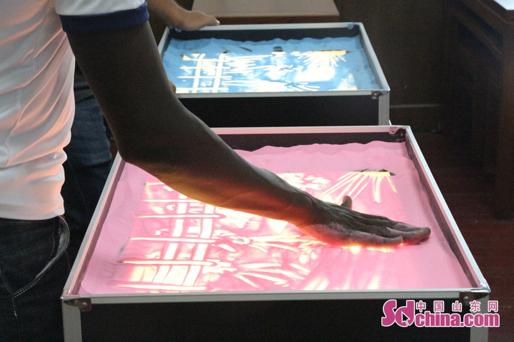 A foreigner draws sand painting in Ni Shan Academy in Daming Lake of Lixia District, Eastern China's Shandong Province. 8 foreigners from different went to Ni Shan Academy to learn sand painting. (Sschina.com/Li Zhen)<br/>