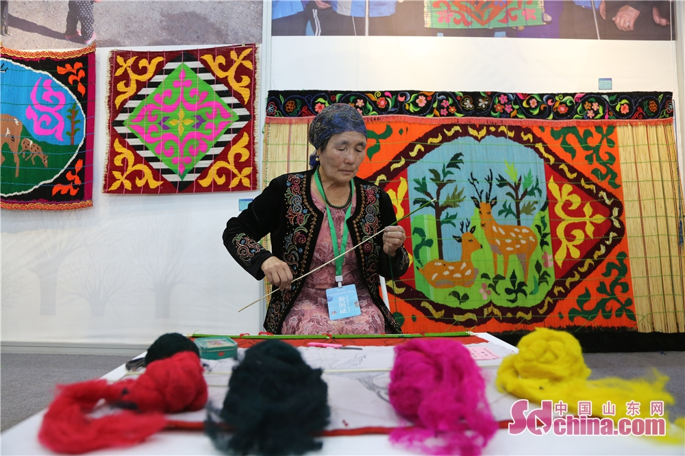 A Kazak ethnic artist showcases her hand knitting in Jinan Shungeng International Convention and Exhibition Center in Jinan, capital of Shandong Province. The Fifth China Intangible Culutral Heritage Expo kicked off in Jinan Shungeng International Convention and Exhibition Center on 13, September, 2118. The expo will continue to 17, September.<br/>