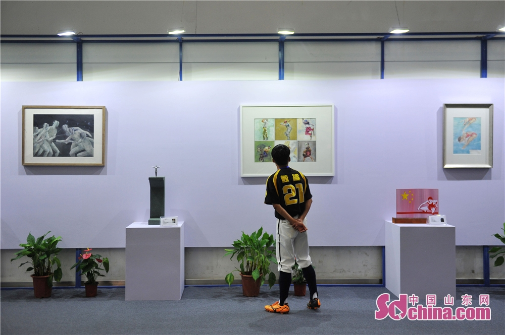 A visitor views artworks during the &quot;Intelligence + Sports&quot; national fitness week in Qingdao. The 2018 Memory of Shibei &quot;Intelligence + Sports&quot; national fitness week kicked off in Qingdao, Shandong Province, on September 20, 2018.<br/>