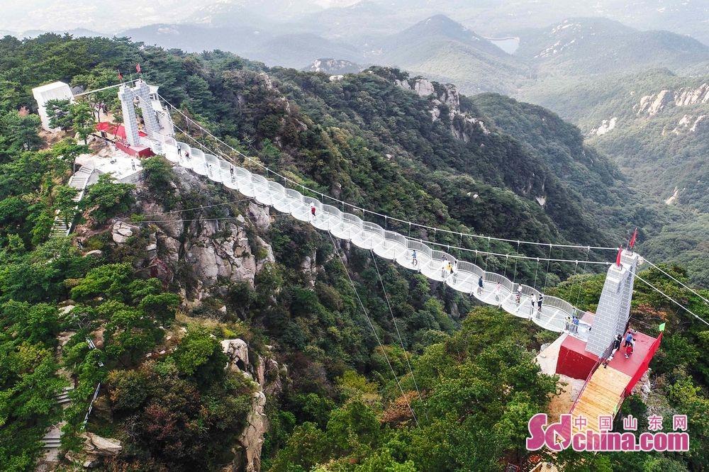 据悉,提升改造后的蒙山5D玻璃桥于近日惊艳亮相,毫无疑问成为沂蒙最高峰上的&amp;ldquo;网红&amp;rdquo;景观。蒙山玻璃桥整体桥面均为钢化玻璃铺设胶合而成,行走在桥面上,玻璃会瞬间&amp;ldquo;碎裂&amp;rdquo;,碎裂的特效会让玻璃桥的体验更加惊险刺激。除此之外,桥面还会出现步步生花、秋风落叶、金龙出没等多种特效,好似漫步梦幻仙境,刺激又浪漫!<br/>