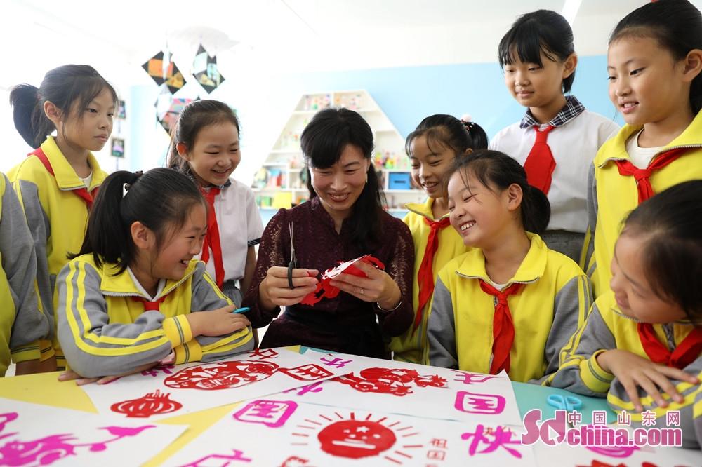 <br/>  9月28日,在山东省荣成市世纪小学,老师在指导学生们剪纸。<br/>
