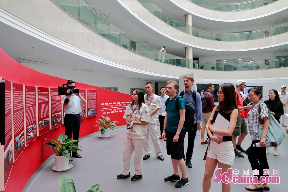 参访团在历史墙处驻足观看,了解中车四方的发展历程。