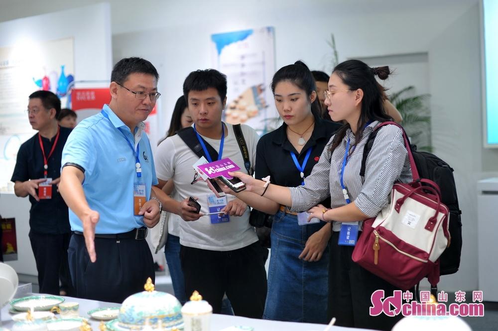 <br/>  在硅元展厅,山东硅元副总经理孙宁向媒体记者介绍上合峰会硅元作品展。