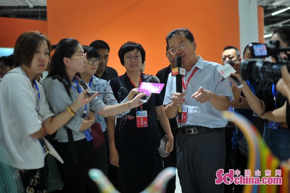 <br/>  淄博市轻工纺织行业协会会长赵鹏向毕荣青介绍深圳玻璃艺术家走进淄博合作成果交流展情况。