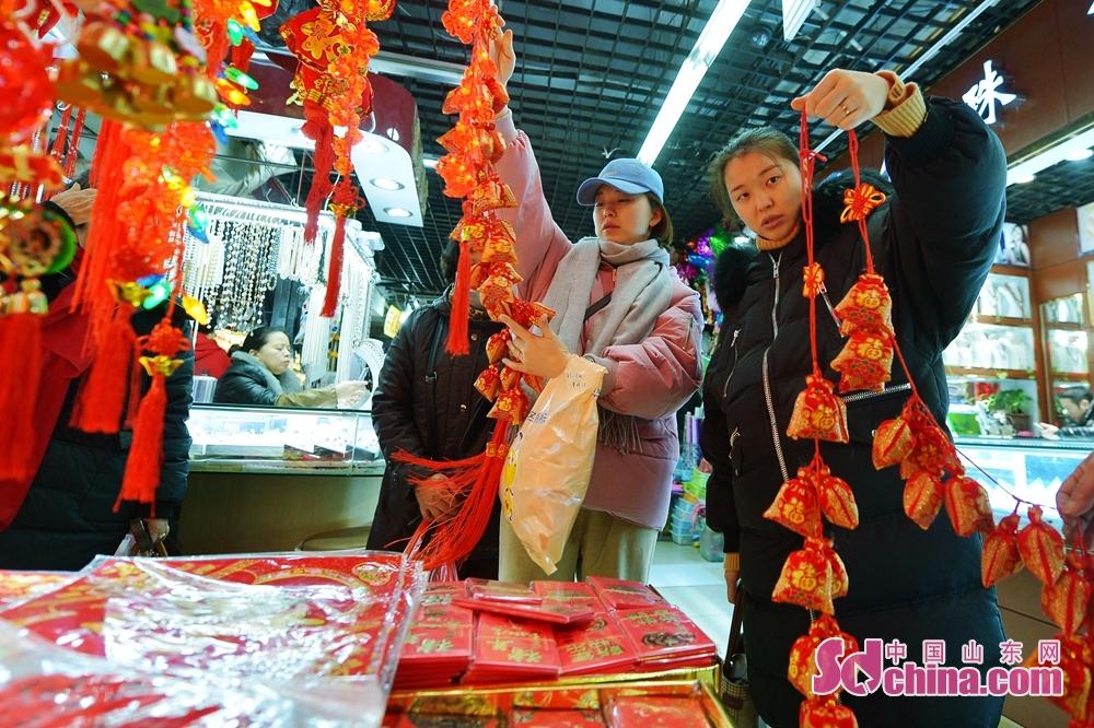 <br/>   1月10日,在青岛市一家小商品批发市场,店家向顾客展示新进的猪年吉祥物。<br/>
