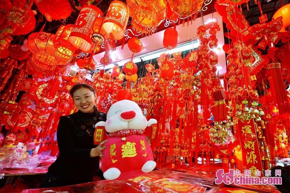 近日,山东青岛的年货市场渐渐红火,春联、挂饰、猪年生肖吉祥物热销,不少市民开始购买年货,迎接新春佳节。<br/>