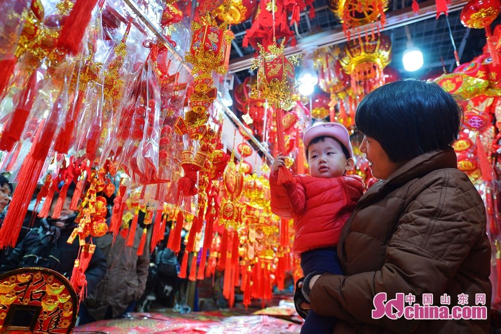 <br/>   1月10日,一名小朋友在青岛市一家小商品批发市场选购猪年吉祥物。<br/>