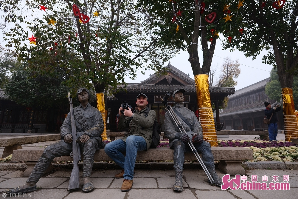 A tourist poses for a photo in the ancient town of Taierzhuang in Zaozhuang, east China&amp;rsquo;s Shandong Province, on January 15, 2019.<br/>