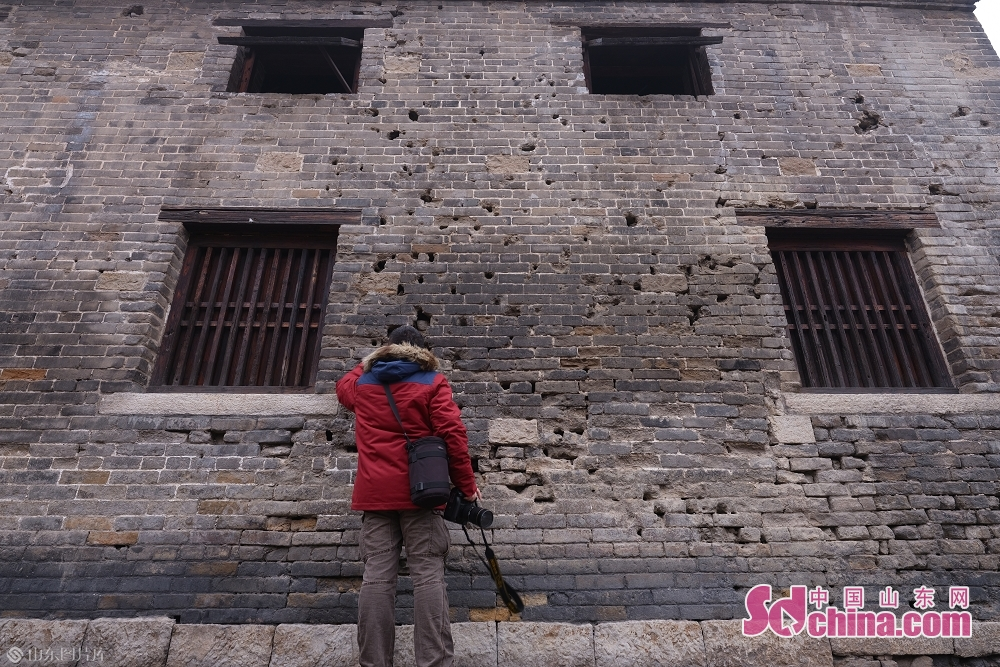 A tourist touches the wall in the ancient town of Taierzhuang in Zaozhuang, east China&amp;rsquo;s Shandong Province, on January 15, 2019.<br/>
