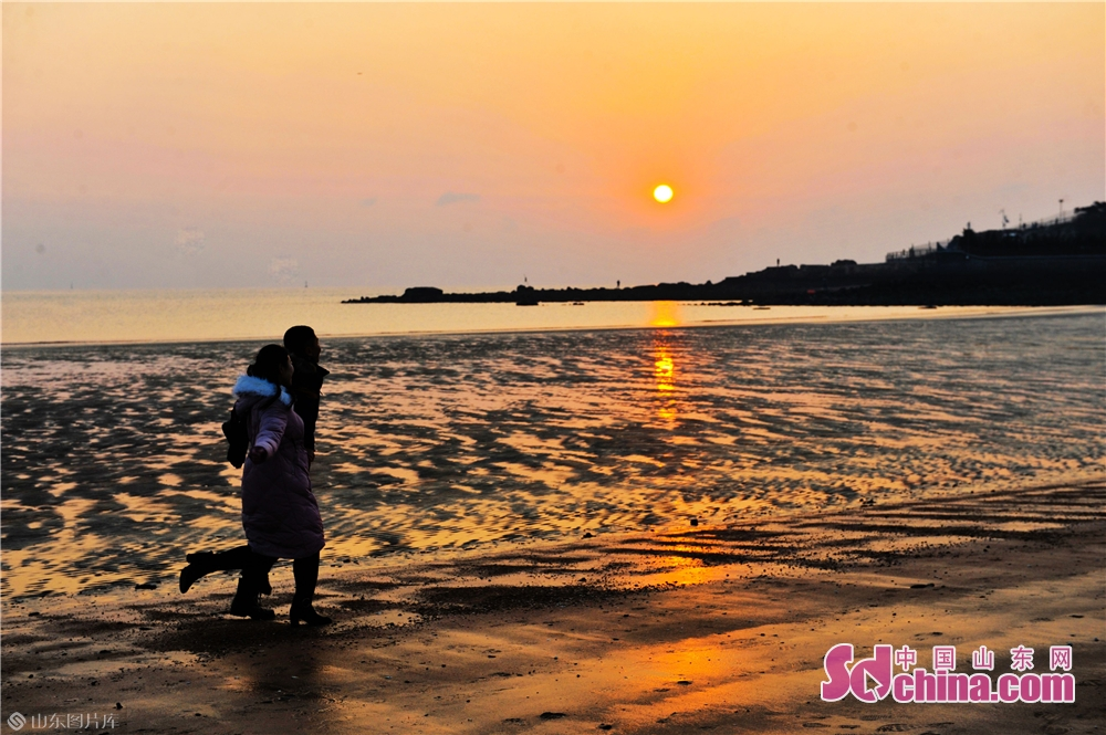 カップルが山東青島海水浴場で日の出を迎えていた。<br/>  中国山東網