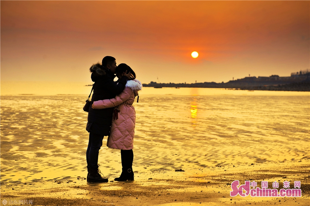 カップルが山東青島海水浴場で日の出を迎えていた。<br/>