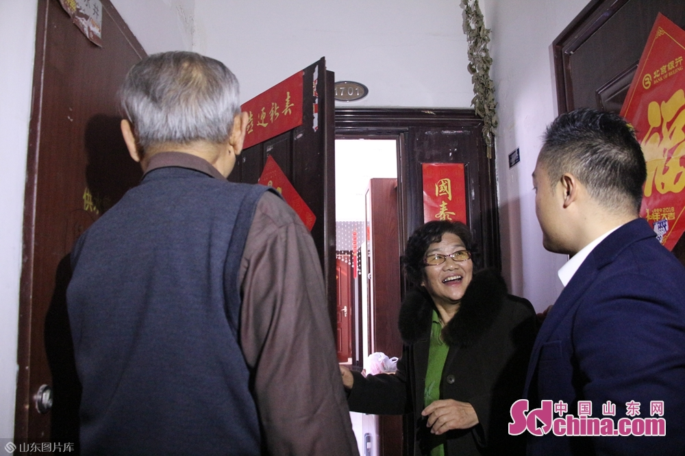 <br/><br/>   工作人员帮助居民把春联贴在了门上,还给他们送去了春节礼品。
